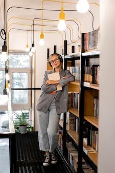 図書館で本を持っている正面図の学生