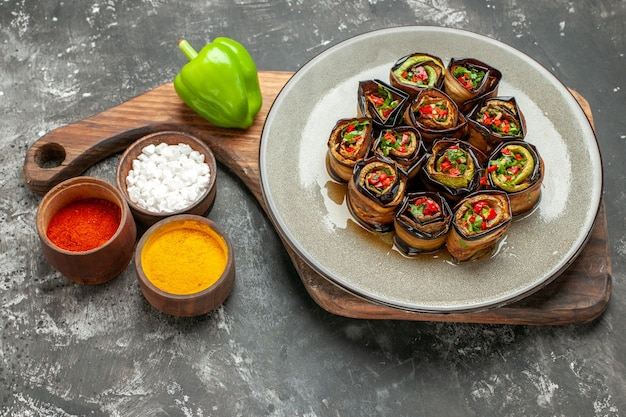 Front view stuffed aubergine rolls in grey oval plate a green pepper on wooden serving board with handle different spices in small bawls on grey background