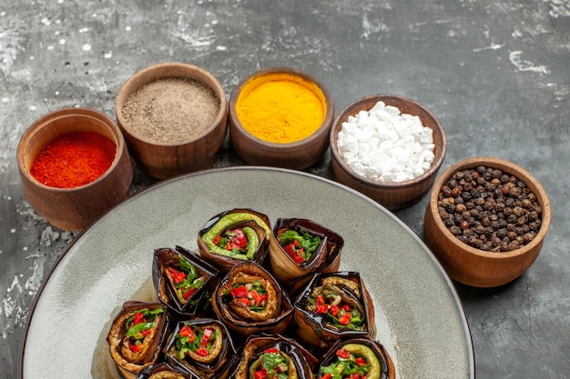 Front view stuffed aubergine rolls hot pepper powder turmeric in small bowls on grey background
