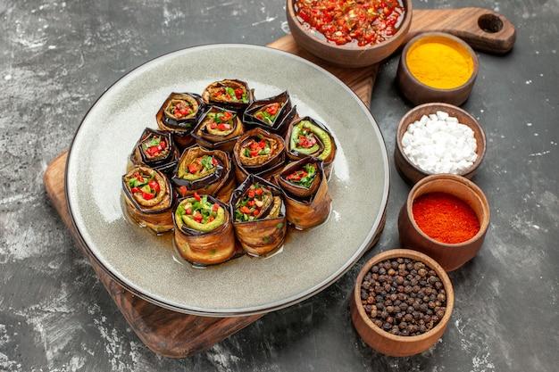 나무 커팅 보드에 있는 그릇에 회색 타원형 접시 adjika에 박제 aubergine 롤 전면 보기