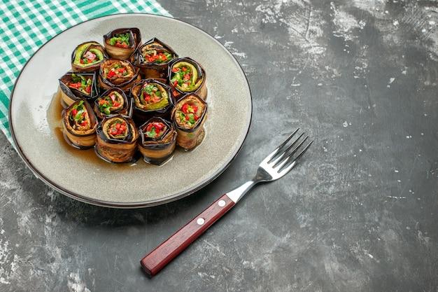 正面図のぬいぐるみ茄子のロールを白い楕円形のプレートターコイズホワイトのテーブルクロスフォークに灰色の背景の自由な場所に