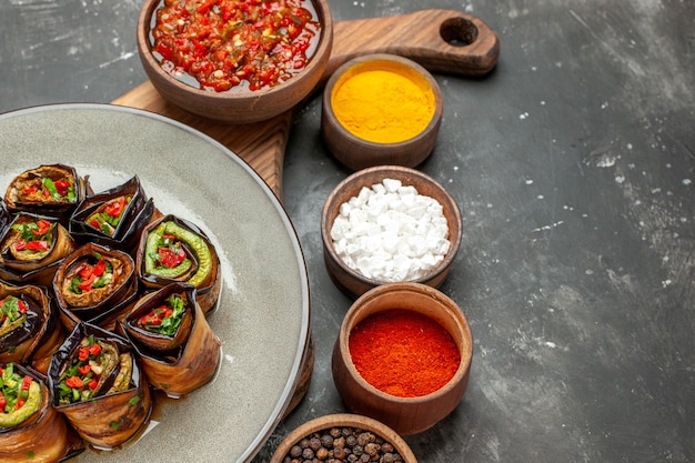 Front view stuffed aubergine rolls in oval plate adjika in bowl on serving board with handle different spices in small bawls on grey background