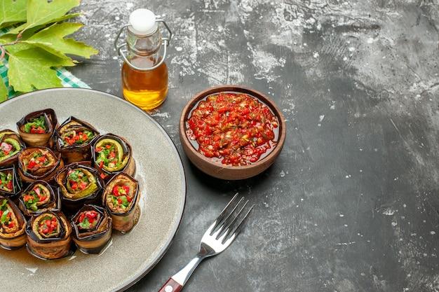 Vista frontale involtini di melanzane ripieni in piatto ovale bianco forchetta olio adjika in una piccola ciotola su sfondo grigio posto libero