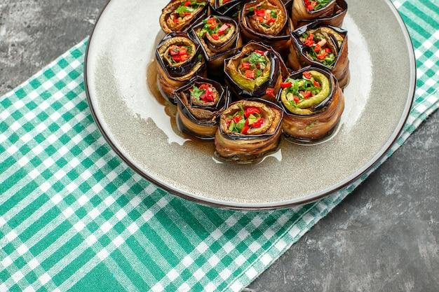 Vista frontale involtini di melanzane ripieni in piatto ovale bianco tovaglia bianco-turchese su piatto grigio foto