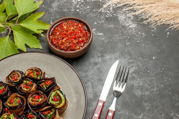 Involtini di melanzane ripieni vista frontale su piastra bianca adjika forchetta e coltello su grigio con spazio copia