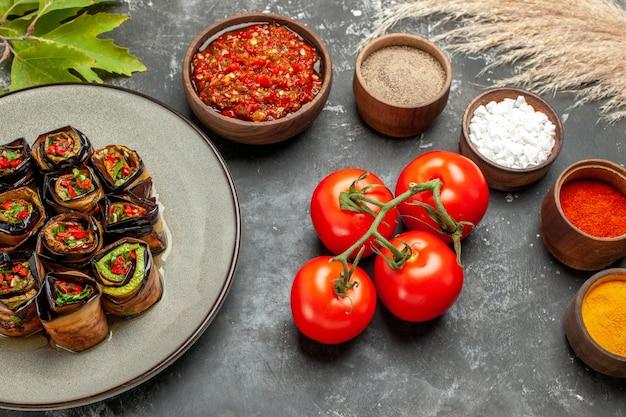 正面図ぬいぐるみ茄子は小さなボウルにスパイスを巻く灰色の背景に塩コショウ赤唐辛子ターメリックアジカトマト