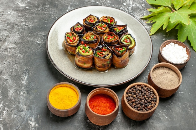 Front view stuffed eggplant rolls on white oval plate different spices in small bowls leaves on grey