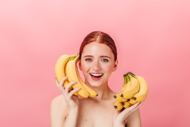 Front view of stunning ginger girl with bananas. studio shot of happy nude woman holding tropical fruits on pink background.