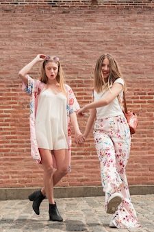 Front view stylish girlfriends walking together