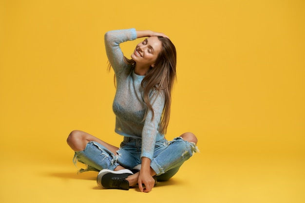 Front view of stylish lady sitting with crossed legs and smiling. attractive young woman in ripped jeans closing eyes and touching hair. isolated on yellow  wall. concept of beauty and joy