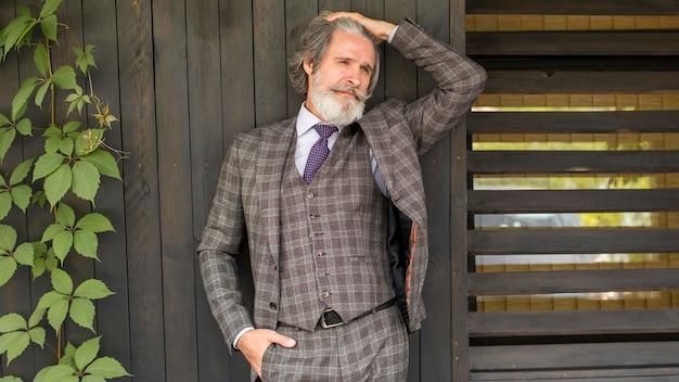 Вид спереди стильный мужчина позирует в костюме