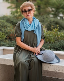 Front view stylish old woman sitting