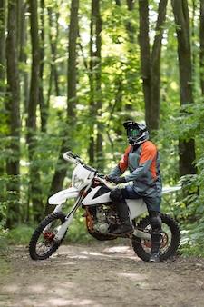 Vista frontale elegante cavaliere in posa con la moto