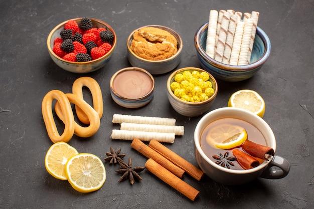 Caramelle di zucchero vista frontale con una tazza di tè e biscotti su sfondo scuro