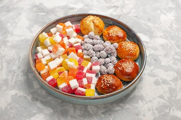 Caramelle di zucchero di vista frontale con i piccoli panini sul biscotto della torta di zucchero del biscotto della pasticceria dolce di superficie bianco-chiaro