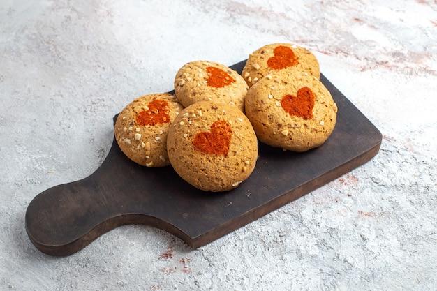 Biscotti di zucchero di vista frontale deliziosi dolci per il tè sulla torta dolce del biscotto dello zucchero della torta di superficie bianca