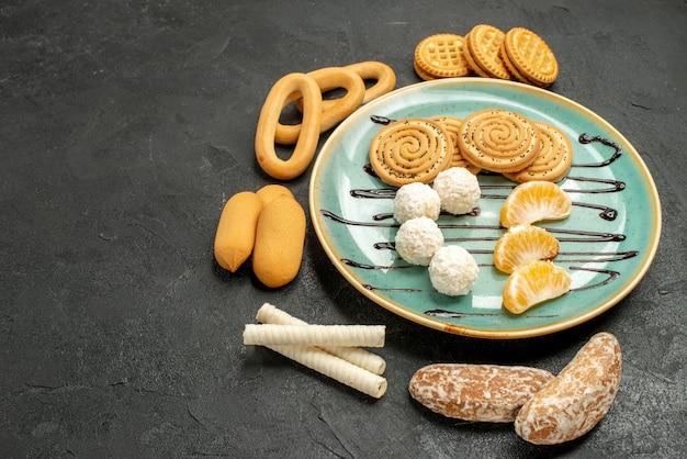 灰色のテーブルケーキビスケットキャンディーにビスケットとキャンディーと正面図のシュガークッキー