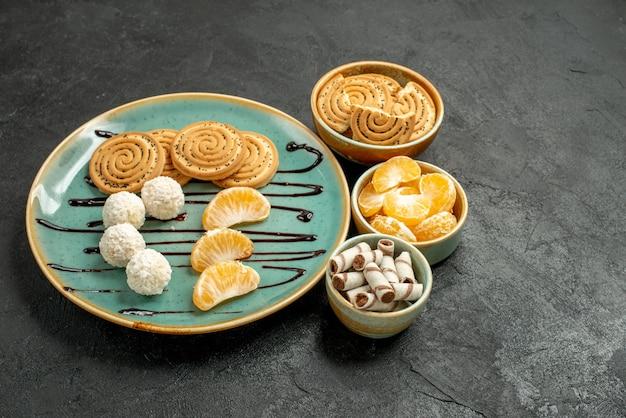 Biscotti di zucchero di vista frontale con le caramelle del cocco sui biscotti del biscotto della tavola grigia dolci
