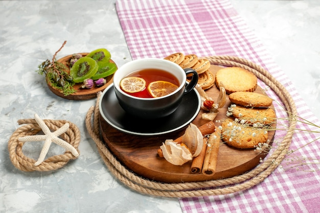 Biscotti di zucchero di vista frontale con la tazza di tè sulla torta dolce della torta del biscotto del biscotto del pavimento bianco