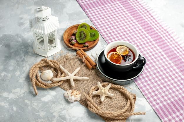 Biscotti di zucchero di vista frontale con una tazza di tè sulla superficie bianca