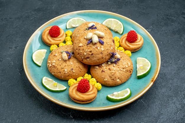Biscotti di zucchero di vista frontale con le fette del limone sulla torta dolce del biscotto della torta di superficie grigia