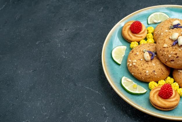 灰色の背景にレモンスライスと正面のシュガークッキーパイクッキービスケット甘いケーキ
