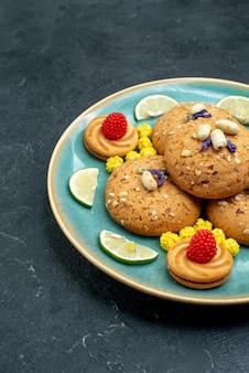灰色の表面にレモンスライスが付いた正面のシュガークッキーパイクッキービスケットスイートケーキ