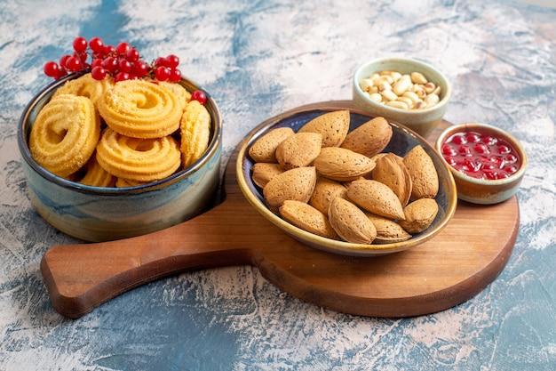 Vista frontale di biscotti di zucchero con noci e marmellata su superficie chiara