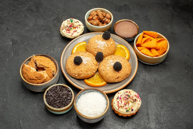 Вид спереди сахарное печенье с дольками апельсина и чипсы на темном фоне печенье, печенье, сладкий чайный торт
