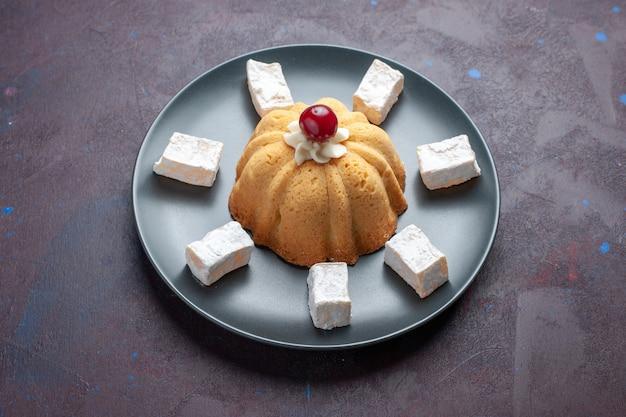 正面図砂糖粉キャンディーおいしいヌガー、暗い表面のプレートの内側にケーキ