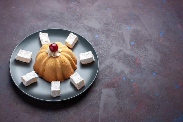 Конфеты из сахарной пудры, вид спереди, вкусная нуга с тортом внутри тарелки на темной поверхности