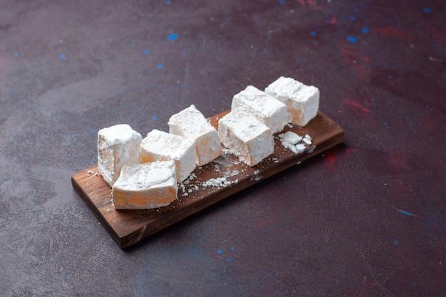 Front view sugar powdered candies nougat on dark surface