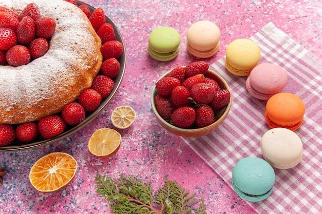 Vista frontale torta di fragole torta di zucchero in polvere con macarons sul rosa