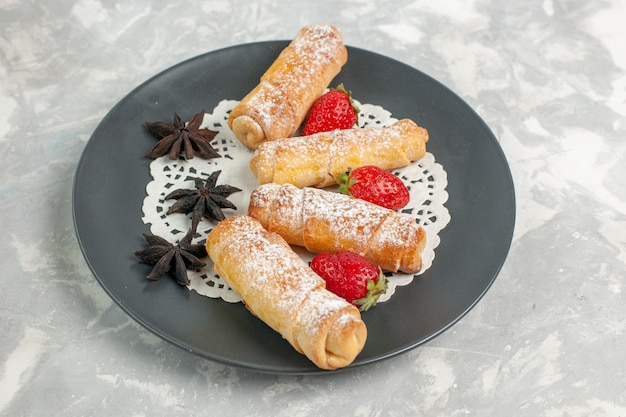 Front view of sugar powdered rolls with strawberries on white wall