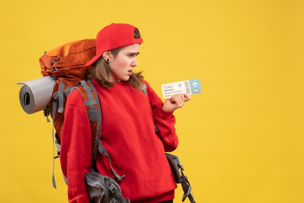 Front view sullen female backpacker holding plane ticket