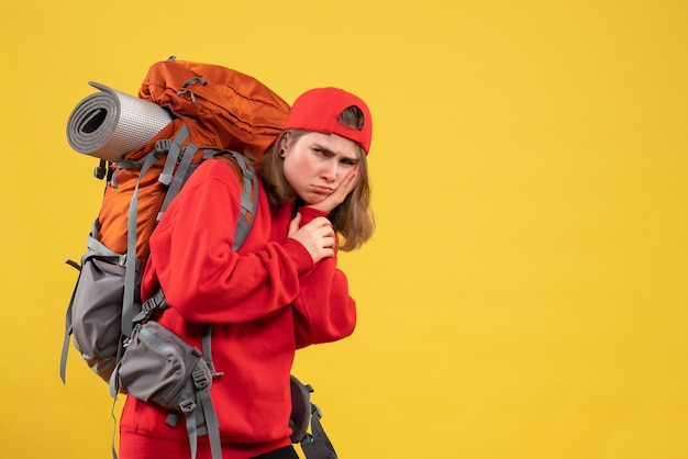 Front view sullen female traveler with backpack holding her face