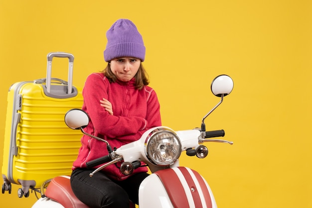 Front view sullen young woman on moped crossing hands