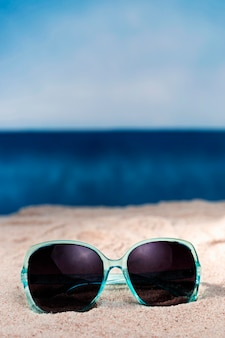 Front view of sunglasses on beach sand with copy space