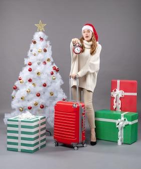 正面図白いクリスマスツリーとプレゼントの近くに赤い目覚まし時計を保持しているサンタの帽子を持つブロンドの女の子を驚かせた