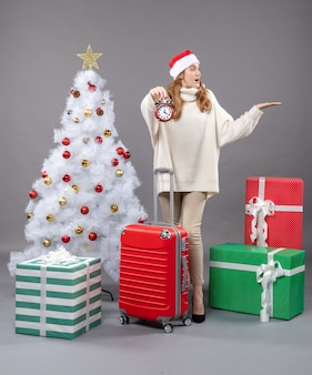 正面図は白いクリスマスツリーと赤いvaliseの近くに赤い目覚まし時計を保持しているサンタの帽子を持つブロンドの女の子を驚かせた