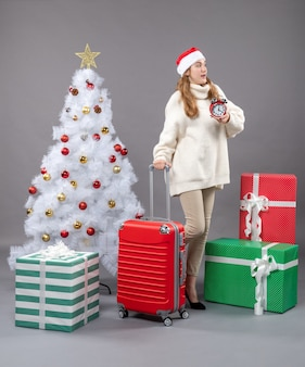 Ragazza bionda sorpresa vista frontale con il cappello della santa che tiene sveglia rossa vicino all'albero e ai regali bianchi di natale