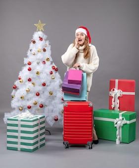 Ragazza bionda sorpresa vista frontale con il cappello della santa che tiene valigia rossa e borse della spesa