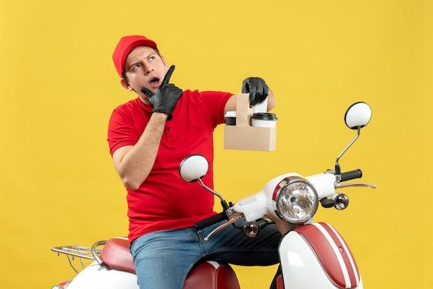 Vista frontale dell'uomo di corriere confuso sorpreso che indossa guanti rossi della camicetta e del cappello nella mascherina medica che consegna l'ordine che si siede sugli ordini della tenuta dello scooter