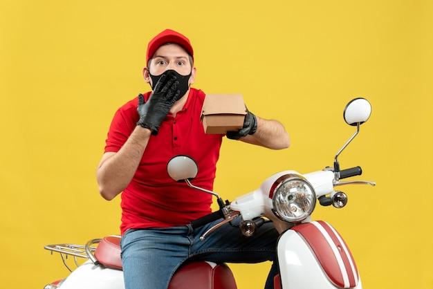 Vista frontale del ragazzo di consegna confuso sorpreso che indossa guanti uniformi e cappello in mascherina medica che si siede sullo scooter che mostra l'ordine