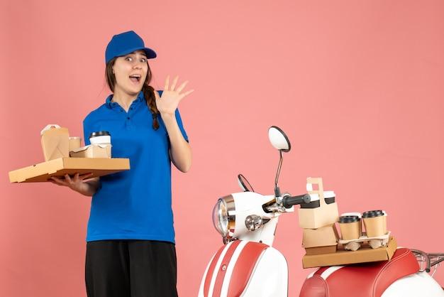 Vista frontale della donna del corriere sorpresa in piedi accanto alla moto con in mano caffè e piccole torte su sfondo color pesca pastello