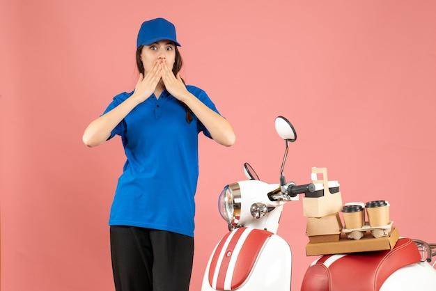 Vista frontale della donna del corriere sorpresa in piedi accanto alla moto con caffè e piccole torte su uno sfondo color pesca pastello