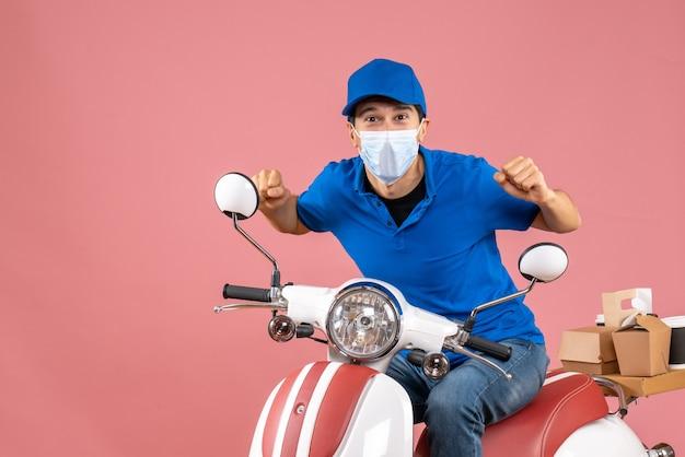 Vista frontale del corriere sorpreso con maschera medica che indossa un cappello seduto su uno scooter che consegna ordini su sfondo color pesca pastello