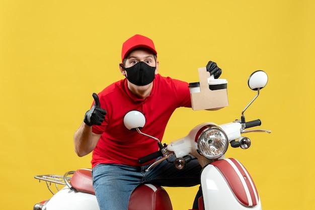 Vista frontale dell'uomo sorpreso del corriere che indossa guanti rossi della camicia e del cappello nella mascherina medica che si siede sullo scooter che mostra gli ordini che fanno il gesto giusto
