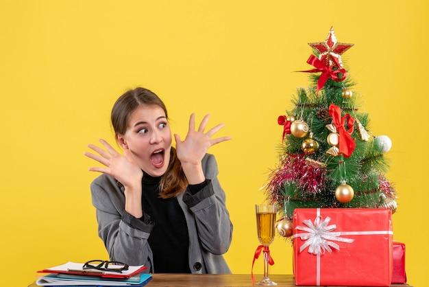 Vista frontale sorpreso ragazza carina seduto alla scrivania con le mani aperte albero di natale e regali cocktail