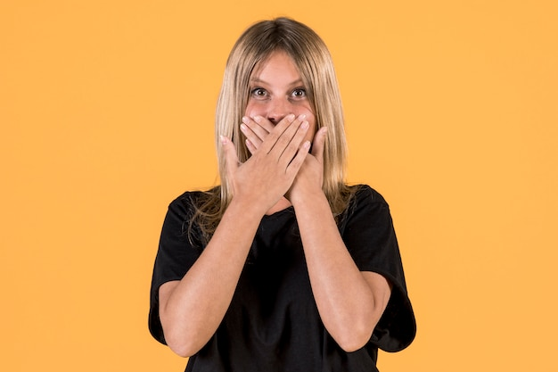 Front view of surprised deaf woman standing in front of yellow background